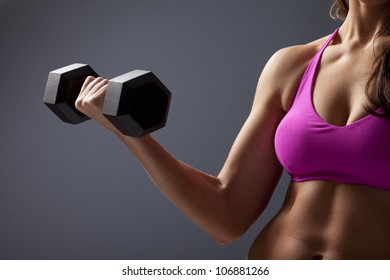 Studio close up photo of young woman lifting dumbbell.