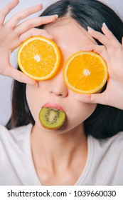 Studio close up portrait of funny young girl holding two orange slices on eyes and kiwi slice in her mouth on white background. Fresh fruits and healthy diet concept.