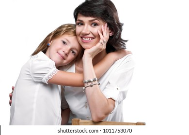 Studio close-up of a beatiful couple: mother and daughter,who huggs her. They look very happy,smiling and wear white t-shirts. Photo was made on white studio background.