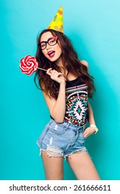Studio closeup colorful portrait of young sexy funny fashion crazy  girl posing on  blue wall background in summer style outfit with pink lollipop wearing paper  hat  and cute glasses.