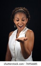 Studio close-up of an excited, lovely, mature black woman with her palm up and extended, parallel to the floor, allowing for easy insertion of products or graphics for her to be holding.