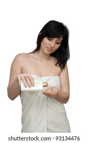 A studio close-up of a lovely young woman wrapped in a white bath towel, pouring lotion into her hand.  Isolated on a white background.