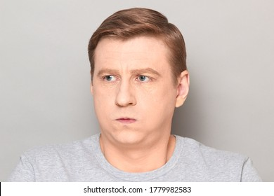Studio close-up portrait of disappointed blond mature man sighing sadly, puffing out his cheeks, pouting lips, making unhappy face, looking frustrated, tired and bored. Headshot over gray background
