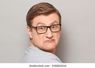 Studio close-up portrait of disgruntled annoyed blond mature man with glasses, grimacing from displeasure, turning around and looking with eyes full of discontent. Headshot over gray background
