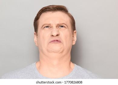 Studio Nahaufnahme eines lustigen blond reifen Mannes, der aus Unbehagen, Ekel und Ekel grimmig ist, einen üblen stinkigen Geruch schnüffelt und etwas Abstoßendes sieht. Headshot auf grauem Hintergrund