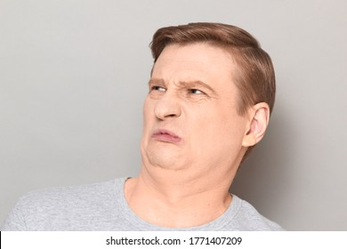 Studio close-up portrait of funny blond mature man grimacing from displeasure, disgust and squeamishness, sniffing nasty stinky smell, seeing something repulsive. Headshot over gray background