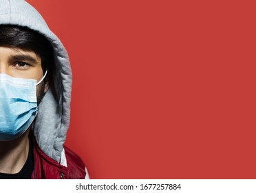 Studio close-up portrait of half face of young hooded guy wearing medical flu mask, protection from coronavirus. Isolated on red background with copy space.