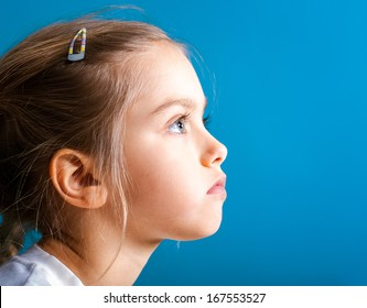 Studio closeup portrait of little girl with serious face in profile