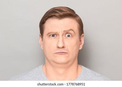 Studio Nahaufnahme eines unglücklich verängstigten blonden Mannes, lustiges Gesicht, verwirrt und verwirrt aussehen. Headshot auf grauem Hintergrund