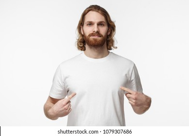 Studio closeup of young handsome bearded male with long fair hair isolated on white background dressed in white blank T-shirt and pointing to it with both hands, positive, copyspace for advertising