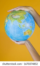 Studio concept with hands holding globe against yellow background