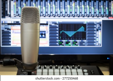 studio condenser microphone, midi synthesizer knob & digital mixer on screen monitor for computer music or broadcasting concept background