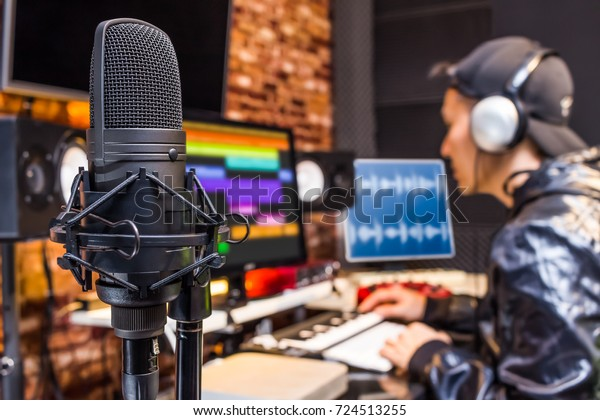 studio condenser microphone on sound engineer working in control room background. recording, broadcasting concept