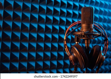 Studio condenser microphone with professional headphones on blue acoustic foam panel background