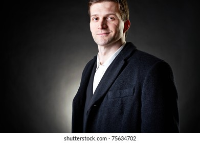 Studio dark portrait of a handsome stylish young man in coat