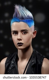 Studio fashion creative model portrait with short colored blue and gray hair.