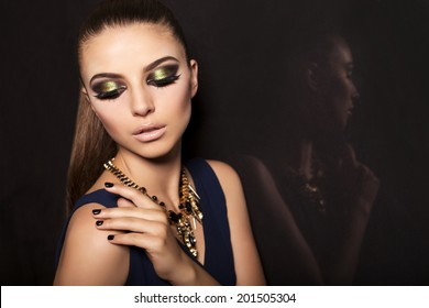 studio fashion photo of beautiful glamour model with dark hair with smokey eyes makeup and accessories