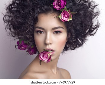 Studio fashion photo of beautiful young woman with flowers in her mouth and hair.  Valentines day. Spring blossom