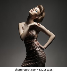 Studio fashion photo of elegant beautiful lady in gold dress. Young sexy woman with art modern haircut.