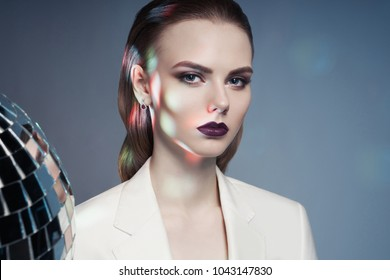 Studio fashion photo of young elegant woman in white men's jacket. Fashion and style. Perfect makeup. Androgyny