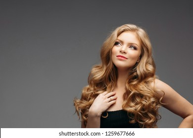 Studio fashion portrait of attractive sensual young woman with long wavy fair hair and blue eyes looking at camera. Natural beauty concept. Caucasian.