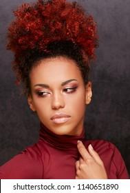 Studio fashion portrait of beautiful african american woman on dark background. Stylish autumn look .