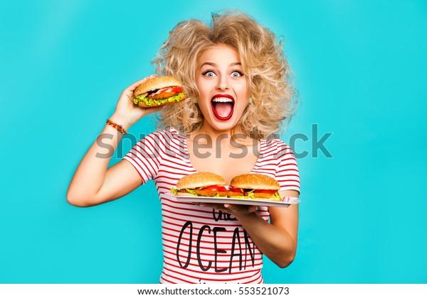 Студия модного портрета красивой забавной молодой девушки на бирюзовом фоне, блондинка держит лоток бургер собирается укусить гамбургер, вьющиеся волосы, идеальный макияж, сумасшедшие эмоции, фаст-фуд