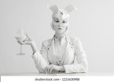 Studio fashion portrait of beautiful lady white rabbit with glass of milk