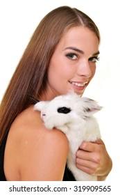 Studio fashion portrait of beautiful lady with white rabbit
