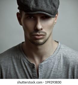 Studio fashion portrait of the handsome man in a cap.