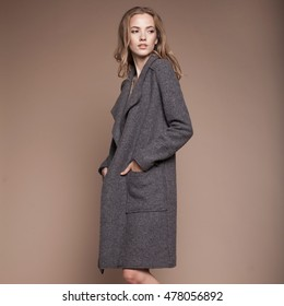 studio fashion portrait of yong pretty blonde woman in  coat on  beige background.
