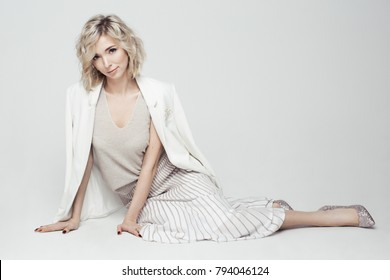 Studio fashion portrait of young beautiful woman with short curly blonde hair in white dress sitting on floor on plain white background / Horizontal / Model in white jacket, top and skirt, silver shoe