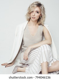 Studio fashion portrait of young beautiful woman with short curly blonde hair in white dress sitting on floor on plain white background / Vertical / Model in white jacket, top and skirt, silver shoes
