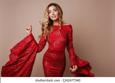 Studio fashion portrait of young blond celebrating woman in luxurious red dress with wide sleeves.  Beige background. New year mood.