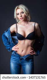Studio fashion shot: a beautiful sexy young woman in jeans and lingerie