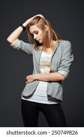Studio fashion shot: a beautiful young girl in leggings, jacket and shirt