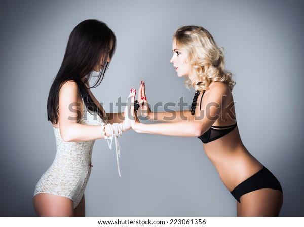 Studio fashion shot: the challenge between two lovely women (blonde and brunette) in underwear