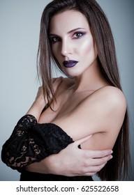 Studio fashion shot: closeup portrait of a pretty young woman. Photo in cold tones