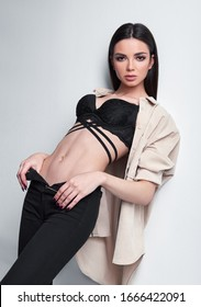Studio fashion shot of the gorgeous young woman. Portrait of beautiful girl dressed in black jeans, brassiere and shirt. Seductive lady against white wall