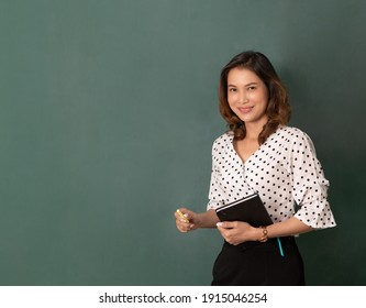 Studio flash light shot, Beautiful Asian woman holding book and chalk standing in front of black board with copy space.