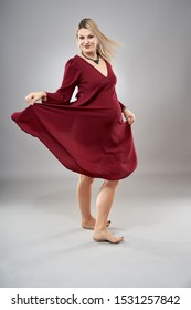 Studio full body portrait of a pregnant woman in red dress