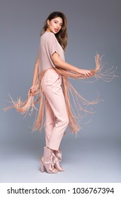 Studio full-body portrait of an expressive model with fringing clothing