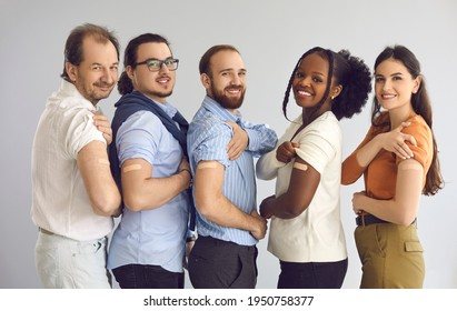 Studio group portrait of happy male and female patients and responsible citizens after getting vaccine. Diverse people show adhesive plasters on arms after vaccination during World Immunization Week