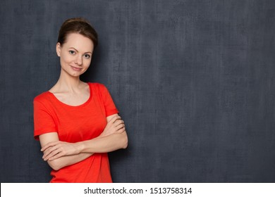 Studio half-length portrait of cute happy satisfied girl wearing orange T-shirt, smiling and looking at camera, being in good mood, crossing arms over body, over gray background, copy space on right