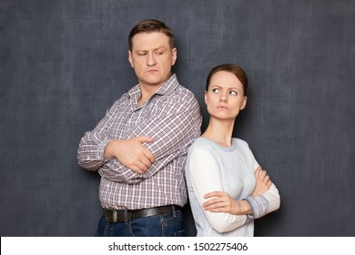 Studio half-length portrait of disgruntled man and woman, standing back to back after quarrel, both are glancing back and looking angrily at one another, over gray background. Relationship concept