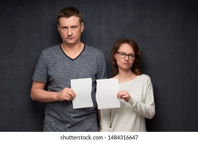 Studio half-length portrait of dissatisfied caucasian couple dressed casually, holding parts of torn white paper sheet in hands, looking with displeasure at camera, standing over gray background