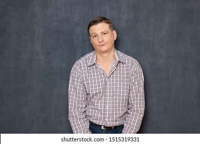 Studio half-length portrait of dissatisfied unimpressed young man dressed in casual clothes, being tired or upset while waiting the results, standing hunched and with hands down, over gray background
