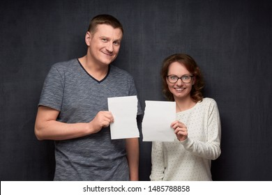Studio half-length portrait of happy caucasian couple dressed casually, holding parts of torn white paper sheet in hands, looking joyfully at camera, standing over gray background