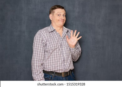 Studio half-length portrait of happy friendly man dressed in casual clothes, waving his hand, greeting kindly and saying hello, looking with silly funny expression at camera, over gray background
