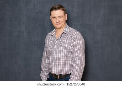 Studio half-length portrait of proud self-confident fair-haired young man wearing shirt and jeans, looking with satisfaction at camera, being sure of successful deal or results, over gray background